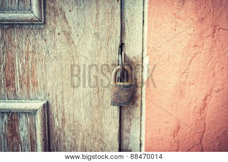 Old And Rusty Padlock On A Wooden Door