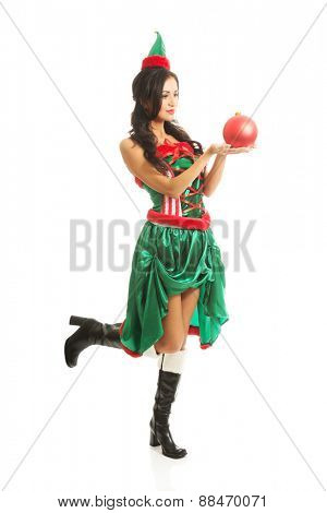 Woman holding red christmas bubble, wearing elf clothes, bending knee.