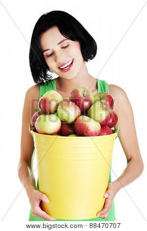 Portrait woman holding bucket full of apples.