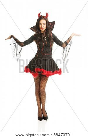 Full length woman standing with open gesture wearing devil clothes.