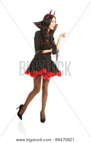 Full length woman wearing devil clothes pointing to the left.