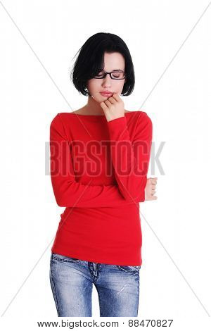 Portrait of sad worried woman with hand on chin.