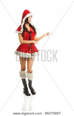 Beautiful slim woman wearing santa clothes and pointing to the left.