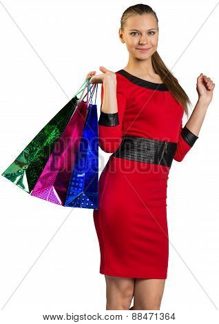 Woman with smile handing shopping bags