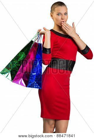 Half-turned woman covering mouth, handing bags