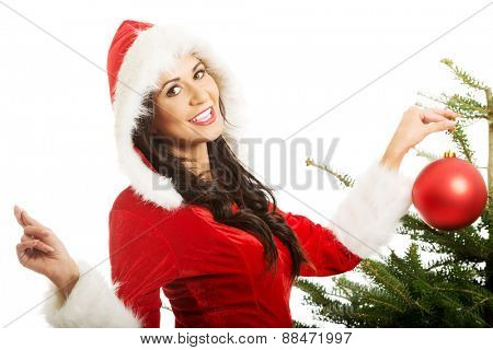 Smiling woman wearing santa claus decorating christmas tree.
