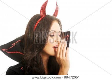 Portrait of woman wearing devil clothes whispering to someone.
