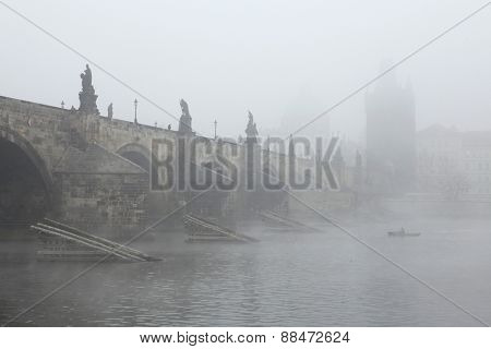 PRAGUE, CZECH REPUBLIC - NOVEMBER 15, 2011: Fisherman fishing from a boat in morning fog near the Charles Bridge in Prague, Czech Republic.