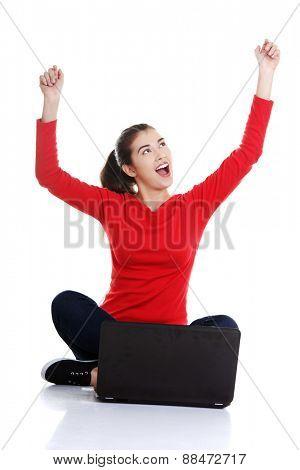 Cheerful woman sitting cross-legged with laptop.