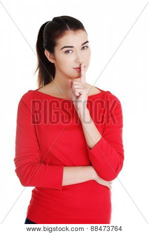 Young caucasian woman making silence sign.