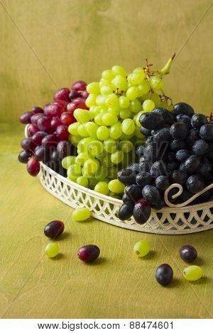 Clusters Of Dark, Red And Green Grapes On A White Tray On A Green Background