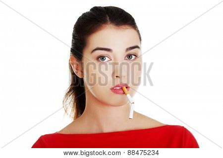Young woman with broken cigarette in mouth.