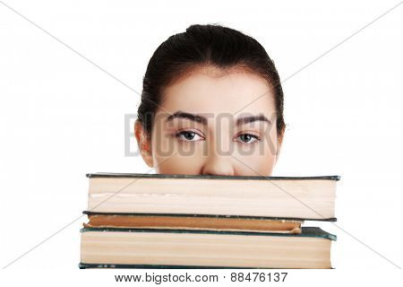 Young student woman hiding behind books.
