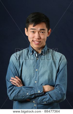 Smirking young Asian man with crossed hands looking at camera