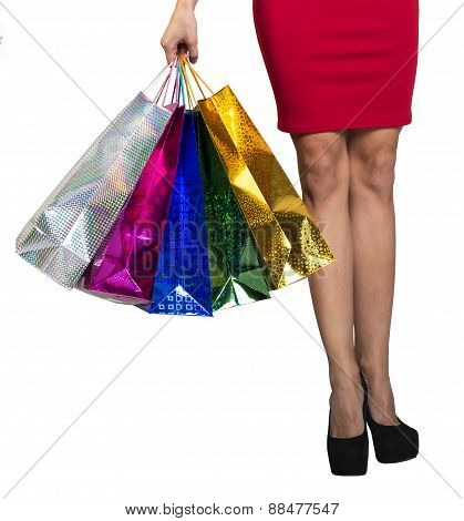 Womans legs and hand holding shopping bags