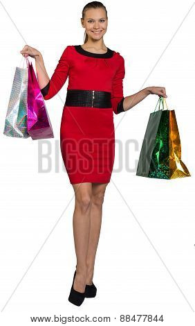 Woman with teeth smile handing bags up