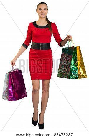 Walking woman with teeth smile handing bags up