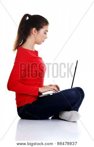 Side view woman sitting cross-legged with laptop.