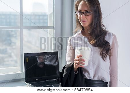 young woman in glasses with the cup of coffee or tea her hands standing near window.