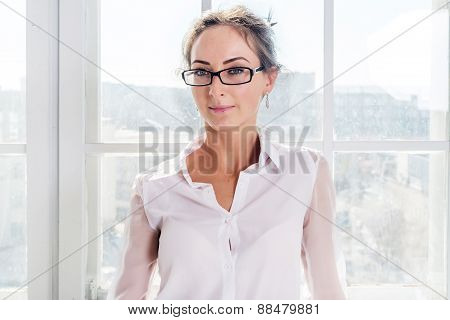 Serious young businesswoman in glasses standing front of the window background
