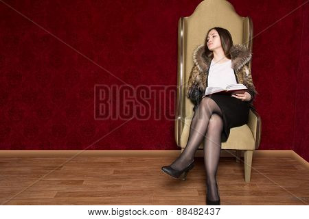 Young Girl In A Fur Coat Sitting Chair With A Book