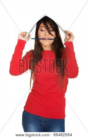 Student woman with notebook on head and pen in mouth.