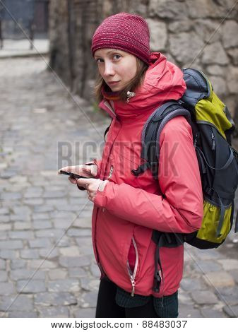The Girl With The Backpack Looks In The Phone.