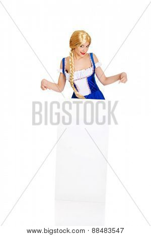 Woman in Bavarian dress pointing on empty banner.