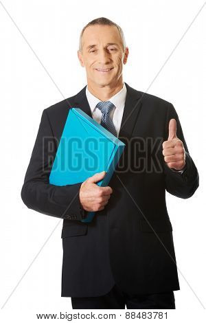 Mature businessman with ok sign holding a binder.