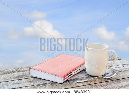 Notebook And Coffee Cup On Wooden Table Over Blurred Sky Background