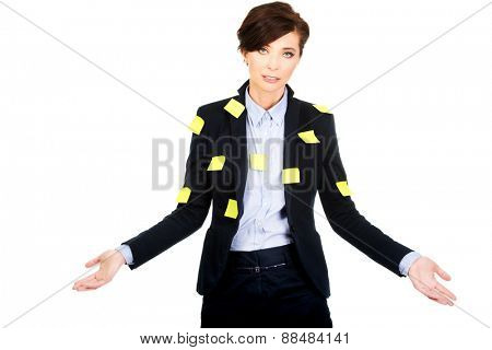 Businesswoman with adhesive cards showing undecided gesture.