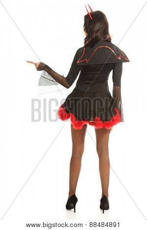 Back view of woman pointing right wearing devil clothes.
