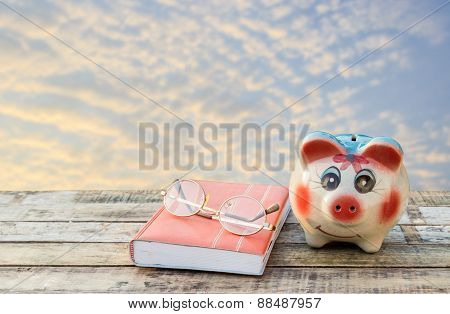 Notebook Glasses And Coffee Cup On Wooden Table And Blurred Sky With Sunlight