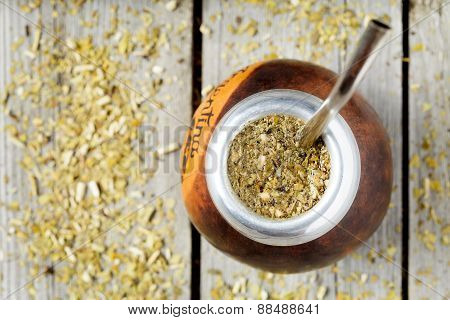 Traditional Argentina yerba mate tea beverage in calabash and bombilla. Rustic style