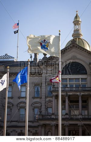 TRENTON, NJ - APRIL 4, 2015: The NJ State Flag flying in front of the New Jersey State House located in Trenton. The capitol building for the state of New Jersey is located on State St.