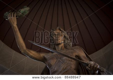 TRENTON, NJ - APR 4 2015: The bronze Lady Victory sculpture featuring a sword and wreath of peace in her hands stands under the NJ World War II Memorial rotunda in Trenton across from the State House.