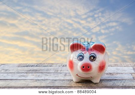 Piggy Bank On Wooden Table Over Blurred Sky Background.