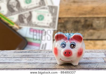 Piggy Bank On Wooden Table Over Blurred Smart Phone And Dollars Background