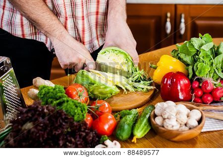Man cuts fresh spring vegetables