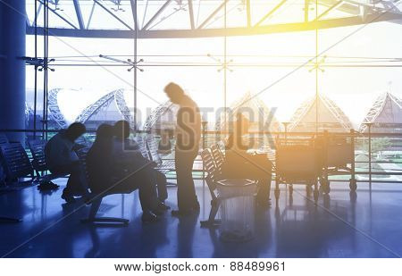 Silhouettes of passengers at airport hall. People in motion blur