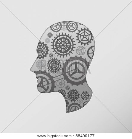 Cog and wheel against silhouette of head