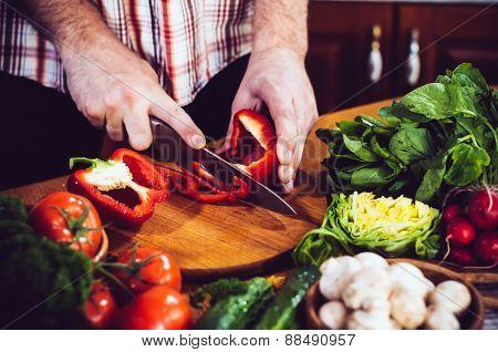 Man cuts fresh spring vegetables