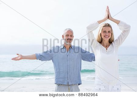 Happy couple doing yoga together at the beach