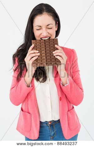 Brunette biting bar of chocolate on white background