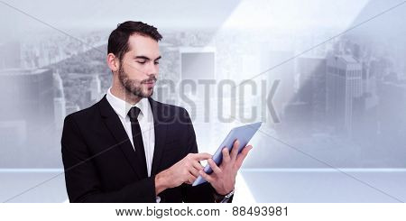 Cheerful businessman touching digital tablet against city scene in a room