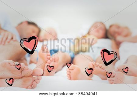 Close up of the feet of a family against red hearts