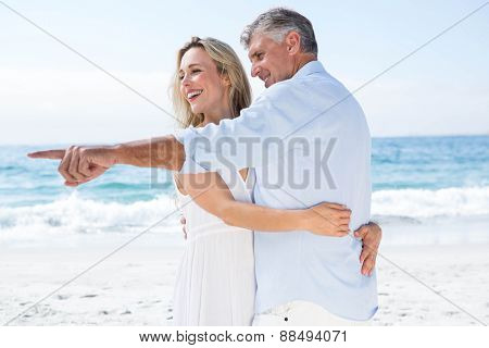 Happy couple hugging each other and pointing something at the beach