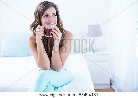 Thoughtful woman drinking a cup of tea at home in the bedroom