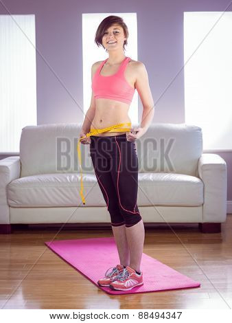 Portrait of happy slim woman measuring waist on a pink floor mat