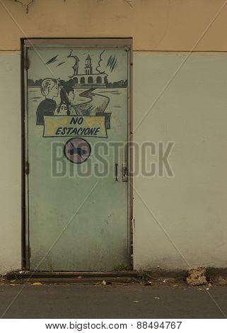 Graffiti On Door In University Wall Prohibiting Car Parking.